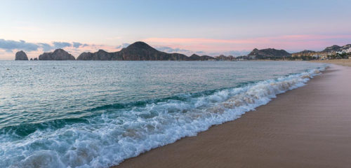 Sunrise on Medano Beach, on the coast of Cabo San Lucas on a Sea of Cortez yacht charter