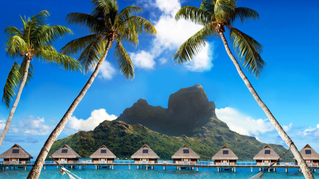 Mountain views and traditional huts on Tahiti yacht charter
