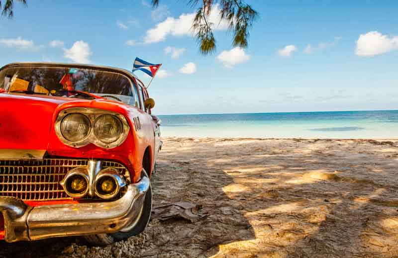 Vintage red car on a beach on a yacht charter itinerary Cuba